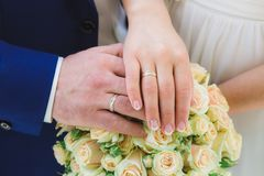 Bride and groom Hands and rings on wedding bouquet Stock Image