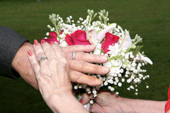 Bride and Groom hands showing rings. Bride and groom oveerlap their hands showing their rings of eternal union Royalty Free Stock Images