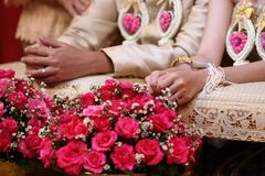 Bride and groom hands in water relaunch ceremony. Thai traditional wedding. Selective focus and shallow depth of field. Stock Photography