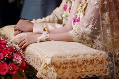 Bride and groom hands in water relaunch ceremony. Thai traditional wedding. Selective focus and shallow depth of field. Royalty Free Stock Image