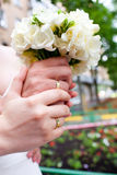 Bride and groom hands and wedding bouquet Stock Photography