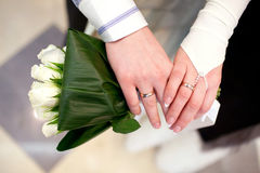 Bride and groom hands and wedding bouquet Stock Images