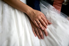 Bride and groom hands. On wedding dress Royalty Free Stock Photography