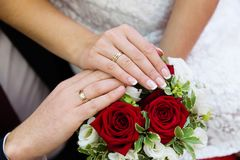 Bride and groom hands with wedding rings. And beautiful bridal bouquet Stock Photography