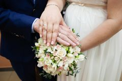 Bride and groom hands with wedding rings. And beautiful bridal bouquet Royalty Free Stock Photos