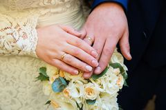 Bride and groom hands with wedding rings. And beautiful bridal bouquet Royalty Free Stock Image