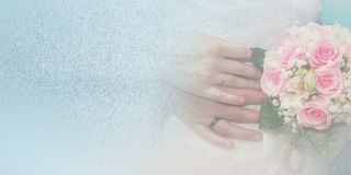 Bride and groom hands with wedding rings and bouquet of roses. On the blue background Stock Photos