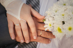 Bride and groom hands with wedding rings and bouquet Royalty Free Stock Photography