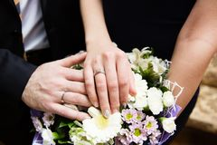 Bride and groom hands with wedding rings. And beautiful bridal bouquet Stock Photos