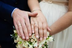 Bride and groom hands with wedding rings. And beautiful bridal bouquet Royalty Free Stock Images