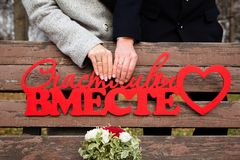 Bride and groom hands with wedding rings. Russian text: happy together Stock Images