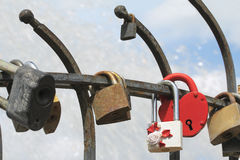 Bride and groom hang a padlock on the bridge as a sign of love Royalty Free Stock Images