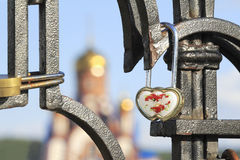 Bride and groom hang a padlock on the bridge near the Church as Royalty Free Stock Photography