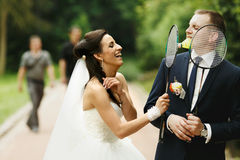 Bride and groom have fun while playing with tennis-rackets Stock Image