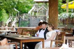 Bride and groom having fun at cafe Royalty Free Stock Photography