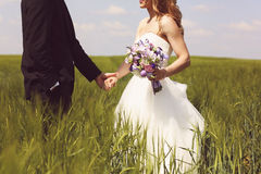 Bride and groom having fun on the fields Stock Image