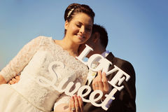 Bride and groom having fun and posing with Sweet Love letters in sunlight Royalty Free Stock Image
