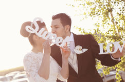 Bride and groom having fun and posing with Sweet Love letters in sunlight Stock Image