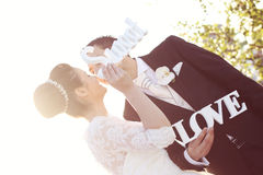 Bride and groom having fun and posing with Sweet Love letters in sunlight Royalty Free Stock Photos