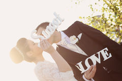 Bride and groom having fun and posing with Sweet Love letters in sunlight Stock Photography