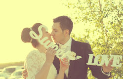 Bride and groom having fun and posing with Sweet Love letters in sunlight Royalty Free Stock Images