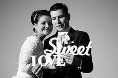 Bride and groom having fun and posing with Sweet Love letters in sunlight Royalty Free Stock Photo