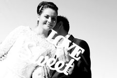 Bride and groom having fun and posing with Sweet Love letters in sunlight Stock Images