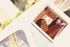 Bride and groom having fun. In a retro car Royalty Free Stock Photography