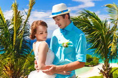 Bride and groom having fun on a tropical beach under the palm tr Stock Photography