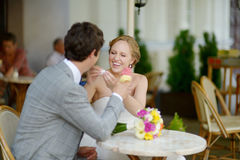 Bride and groom having an ice cream outdoors Royalty Free Stock Photos