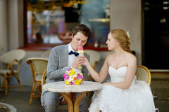 Bride and groom having an ice cream outdoors Stock Image