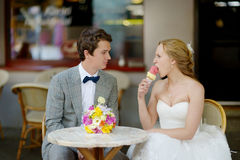 Bride and groom having an ice cream outdoors Royalty Free Stock Images