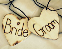 Bride and groom hearts. Words bride and groom emblazoned on wooden love heart shapes Stock Image