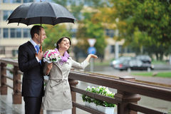 Bride and groom hiding from the rain, while catching raindrops a. Wedding couple hiding from the rain, while catching raindrops and smiling Royalty Free Stock Photos