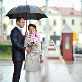 Bride and groom hiding from rain in an old town Stock Photo