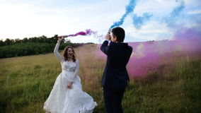 The bride, the groom and his friend posing in a field with smoke bombs. stock video footage