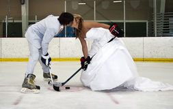 Bride and Groom hockey face off. A just married bride and groom kissing during a hockey face off challenge Royalty Free Stock Photo
