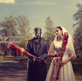 Bride and groom in hockey mask, maniac family. Bride and groom in hockey mask holding bloody bats in their hands. Maniac family Stock Images