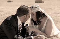 Bride and groom hold a dialogue on a bale of straw Royalty Free Stock Photography