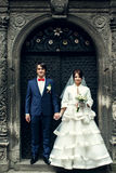 Bride and groom hold each other hands standing behind an old ste. El door Stock Image