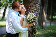 Bride and groom hold each other hands while they walk along the stock images