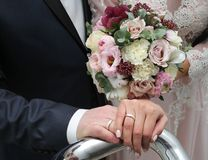 Bride and groom hold each other`s hands. bride`s bouquet. Close-up Stock Photography