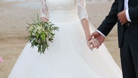 The bride and groom hold hands. The bride has a bouquet in her hands. stock video
