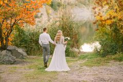 Bride and groom hold hands, go along the path to the water in autumn forest, girl with blond hair in a gray gorgeous. Dress with long wonderful train next to a royalty free stock photo