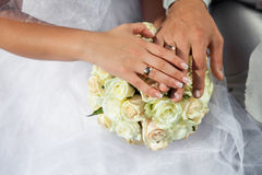 Bride and groom hold hands with golden wedding rings above wedding bouquet from white roses, cream flowers. stock images