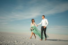 Bride and groom hold hands, laugh cheerfully and walk barefoot i. N desert. Bride is dressed in wedding dress and with bouquet. They going on background of white royalty free stock photo