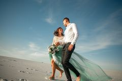 Bride and groom hold hands, laugh cheerfully and walk barefoot i. N desert. Bride is dressed in wedding dress and with bouquet. They going on background of white stock photo