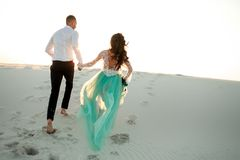 Bride and groom hold hands and run on sand in desert. Back view. Bride and groom hold hands and running uphill on sand dune in desert. Back view Royalty Free Stock Photography