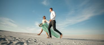 Bride and groom hold hands, smile and walk barefoot in desert. W Stock Photos