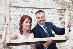 Bride and groom hold portrait frame Royalty Free Stock Photo